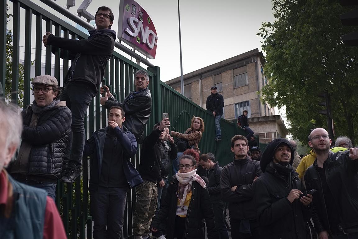 1er mai 2018 à Paris, des heurts ont éclaté en marge du défilé syndical. Des passants tentent d'apercevoir ce qu'il se passe.