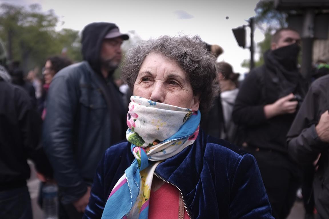 1er mai 2018 à Paris, un dame de 82 ans passe au milieu des Black Blocs