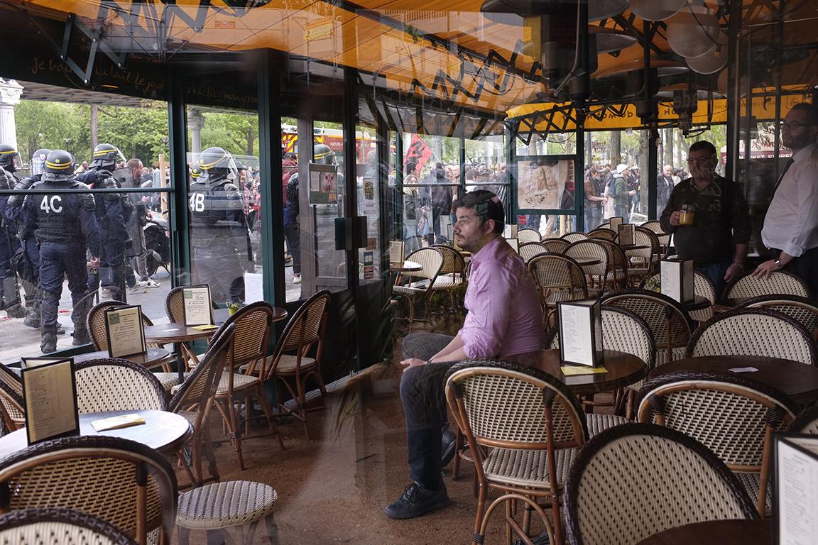 1er mai 2018 à Paris, un bistrotier regarde depuis son café les échauffourées entre CRS et Black Blocs
