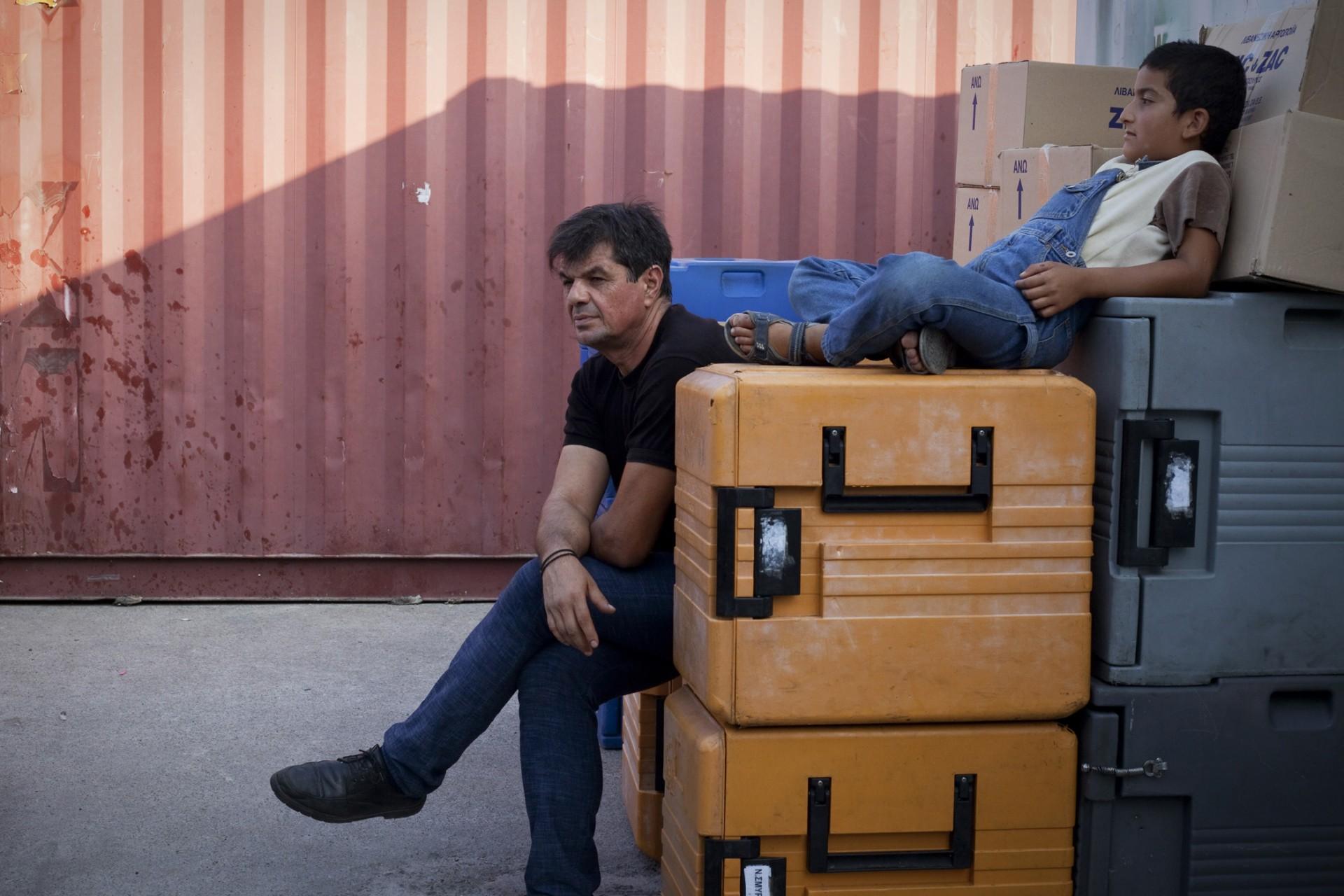 Un bénévole grec et un enfant migrant attendent à l'ombre le moment de commencer la distribution des repas.