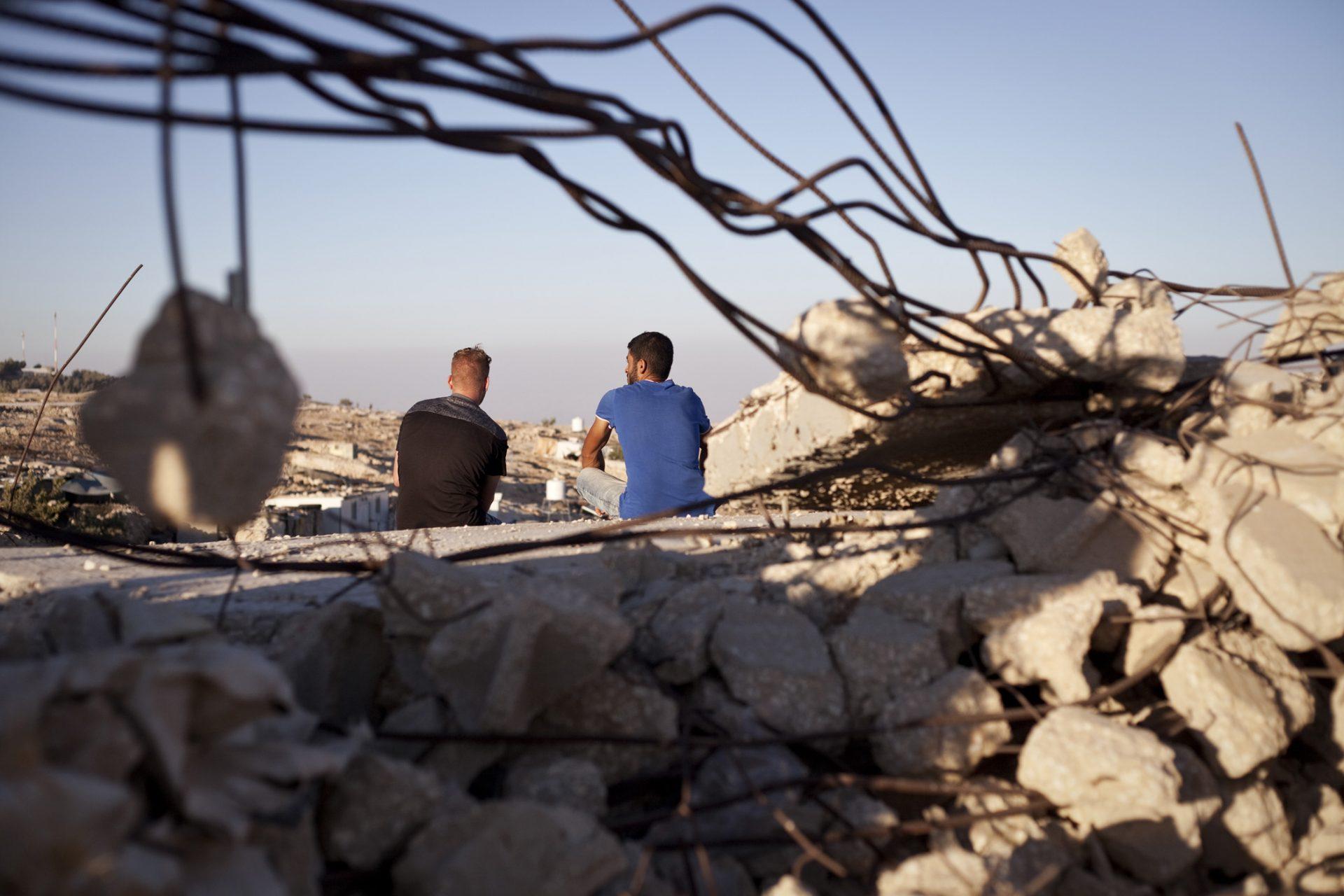 Deux habitants d'At-Tuwani sont assis sur les ruines de la mosquée du village. Le village étant situé dans une zone classée militaire par Israël, toute nouvelle construction y est interdite, et les permis de construire sont systématiquement rejetés. Les nouvelles constructions faites sans permis sont régulièrement détruites par l'armée.